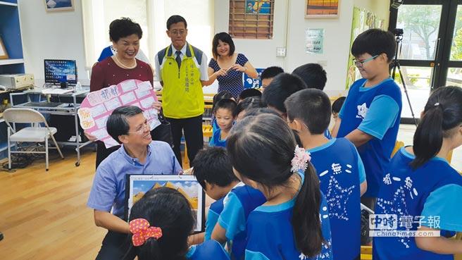 精湛建設總經理陳志聲為溪洲國小孩子們導讀10月刊物【未來兒童】的「偉大的建築」,引導孩子進入閱讀的世界。圖/王妙琴